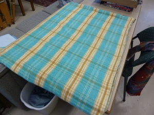 The blue blanket before sewing in a tube and cutting the strups