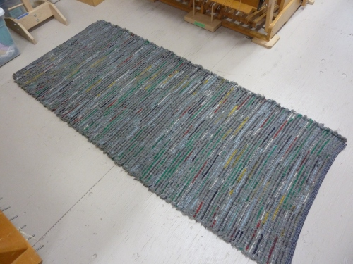 R186 - a long rug, gray fringe alternated with colorful wooly worms