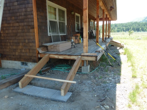 Two stairs off the back porch, one from the French doors and one leading to the woodpile